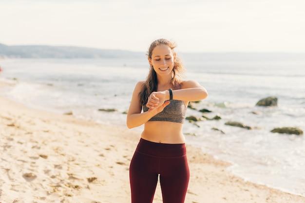 スポーツウェアを着た若い女性が手首のスマートウォッチでデータをチェックしています。