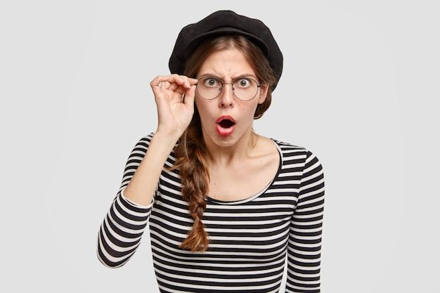 Giovane donna che indossa camicia a righe e berretto