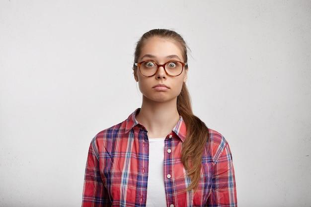 Giovane donna che indossa camicia a righe e occhiali da vista