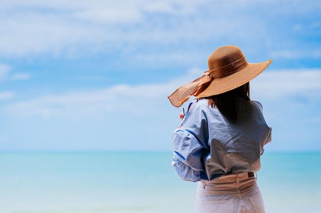 태국 해변에서 푸른 하늘이 세련된 파란색 드레스와 밀짚 모자를 착용하는 젊은 여자.