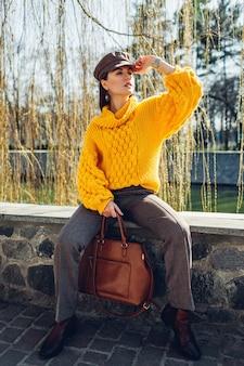세련 된 옷을 입고 야외에서 핸드백을 들고 젊은 여자. 봄 여성 의류 및 액세서리. 스트리트 패션. 2021 년의 색