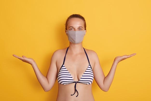 Giovane donna che indossa costumi da bagno a strisce alla moda e maschera medica contro il muro giallo, diffondendo entrambe le mani da parte