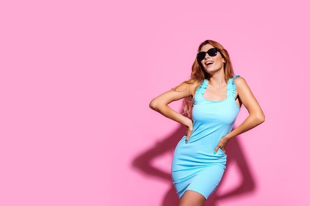 ピンクのスタジオの背景にポーズをとってサングラスとドレスを着て若い女性