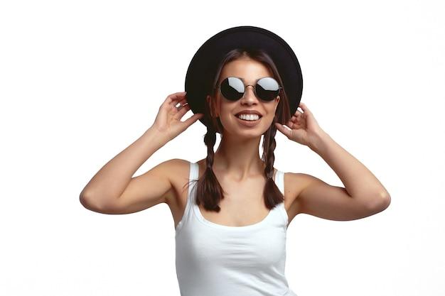Молодая женщина в солнцезащитных очках и шляпе улыбается и трогает шляпу над белой стеной