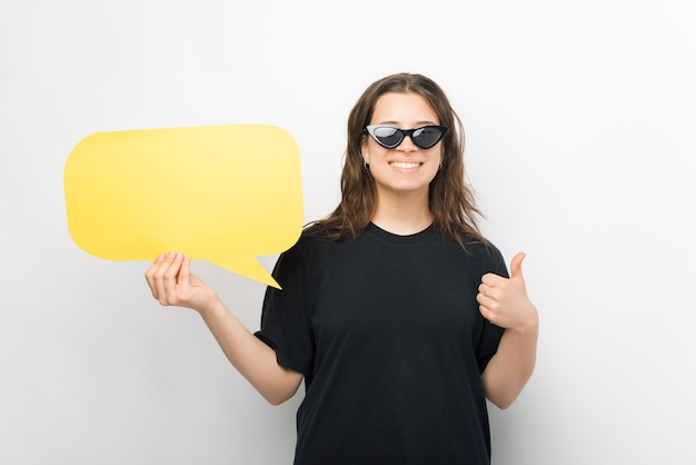 Young woman wearing sunglasses is holding a speech bubble and showing thumb up.