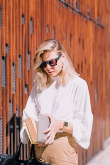 Young woman wearing sunglasses standing outside opening the book