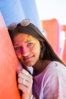 Young woman wearing sunglasses with her face covered with holi color looking at camera