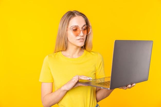 Молодая женщина в футболке показывает портативный компьютер, изолированный на желтом