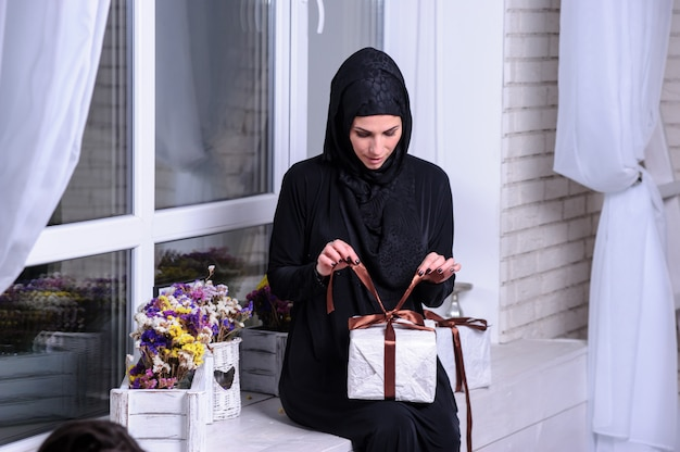 Young woman wearing traditional arabic clothing with gift in hands.