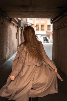 都市の古い通りを歩いてトレンディな茶色のコートを着た若い女性