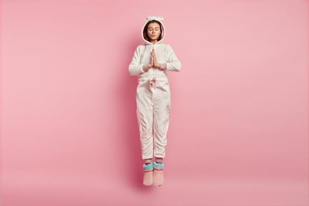Young woman wearing unicorn pajamas