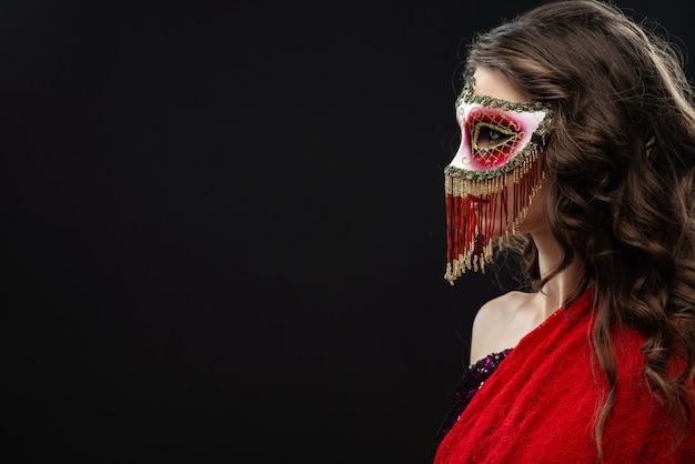 Young woman wearing venetian carnival mask against black background sideway