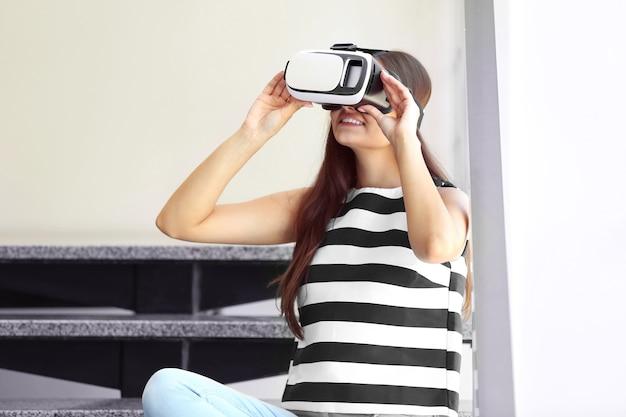 仮想現実の眼鏡をかけて階段に座る若い女性