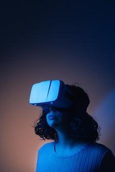 バーチャルリアリティ眼鏡をかけている若い女性。未来的な環境。コピースペース。
