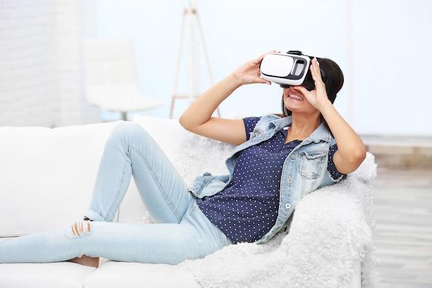 部屋のソファにバーチャルリアリティ眼鏡をかけている若い女性