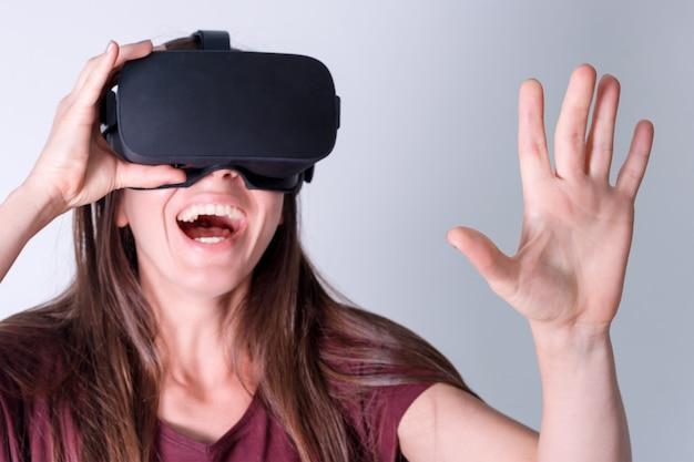 仮想現実を身に着けている若い女性は、ヘッドセット、vrボックスをゴーグルします。接続、技術、新世代、進歩のコンセプト。バーチャルリアリティでオブジェクトに触れようとしている女の子。灰色で撮影スタジオ