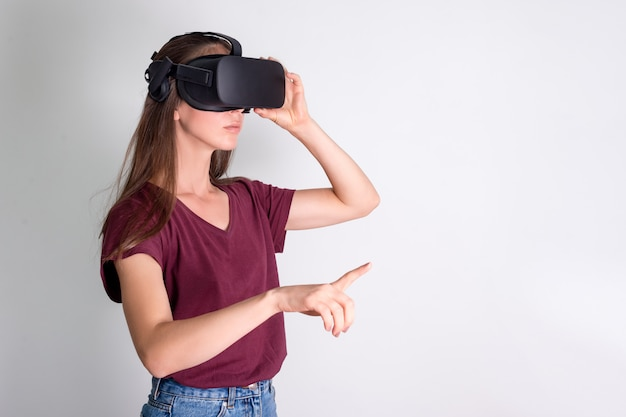 Young woman wearing virtual reality goggles headset, vr box. connection, technology, new generation, progress concept. girl trying to touch objects in virtual reality. studio shot on gray