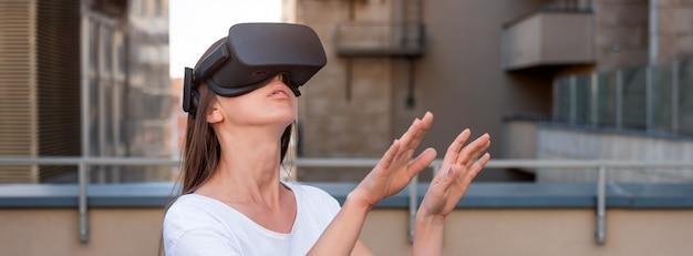 仮想現実を身に着けている若い女性はヘッドセット、vrボックスを屋外にゴーグルします。接続、技術、新世代、進歩のコンセプト。バーチャルリアリティでオブジェクトに触れようとしている女の子