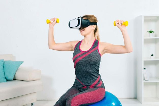 Young woman wearing the virtual reality headset sitting on the fitness ball exercising with yellow dumbbells