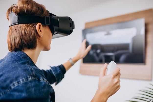 Giovane donna che indossa occhiali vr e giocare a gioco virtuale tramite telecomando