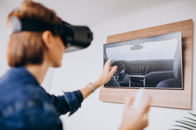 Young woman wearing vr glasses and playing virtual game using remote