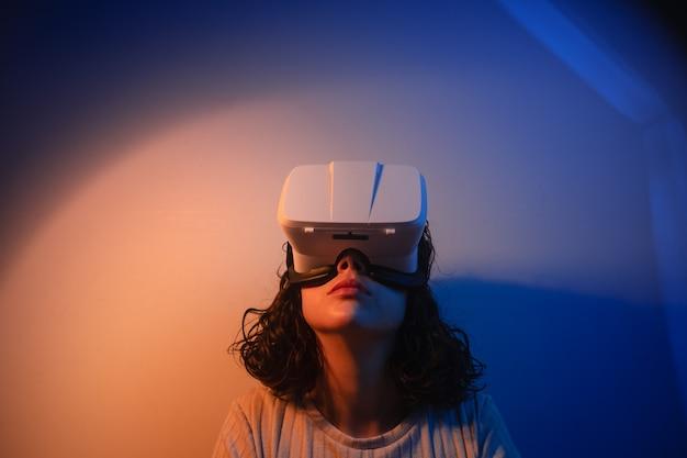 Молодая женщина в очках vr. виртуальная реальность. футуристическая среда. досуг дома