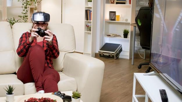 ビデオゲームをプレイしながらvrヘッドセットを身に着けている若い女性。ゲーミングチェアに座っている彼氏。
