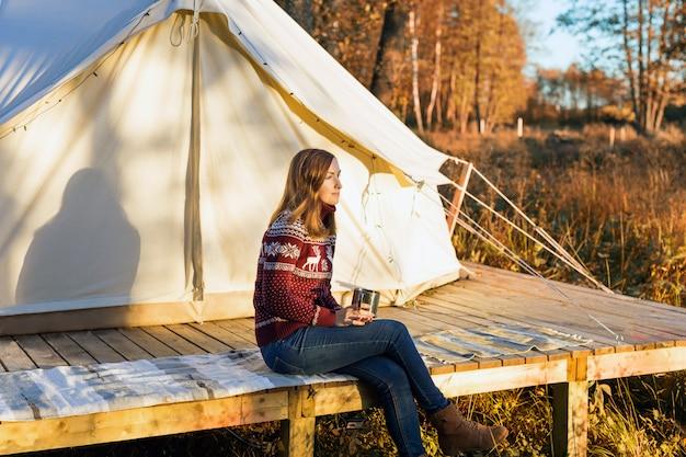 Молодая женщина, одетая в теплую майку, пить кофе, сидя возле палатки