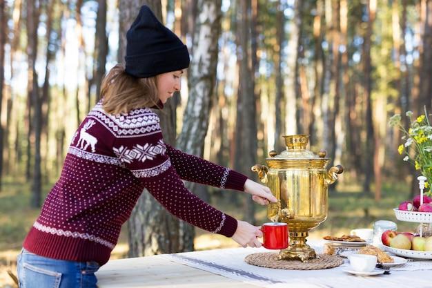 森でヴィンテージのサモワールを使用していくつかのお茶を注ぐ暖かいジャージを着た若い女性