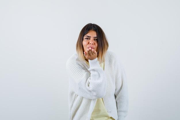 Giovane donna che indossa un cardigan bianco che soffia un bacio