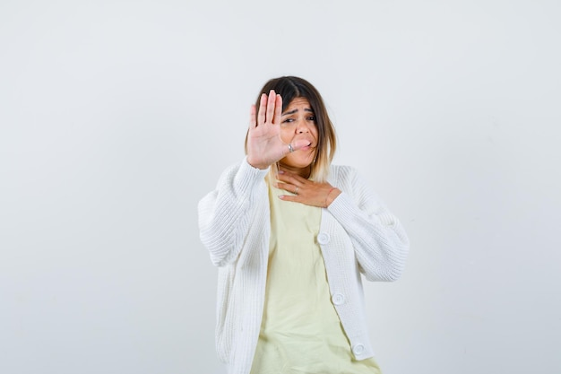 Giovane donna che indossa un cardigan bianco che mostra il gesto di arresto