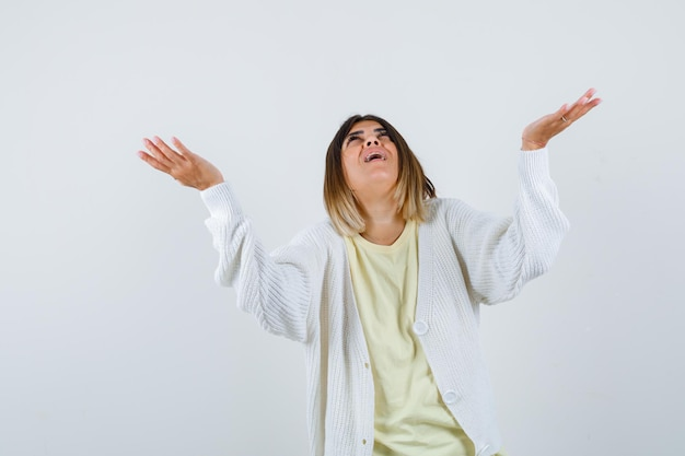 Young woman wearing a white cardigan with hands up