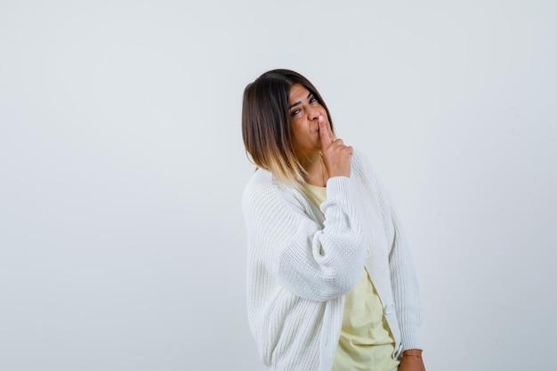 Giovane donna che indossa un cardigan bianco