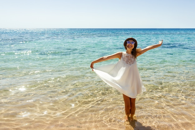 Young woman wearing a white dress and hat standing on a beach and enjoying the sun