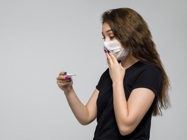 La giovane donna che indossa la maschera medica bianca è sorpresa dopo aver esaminato un termometro