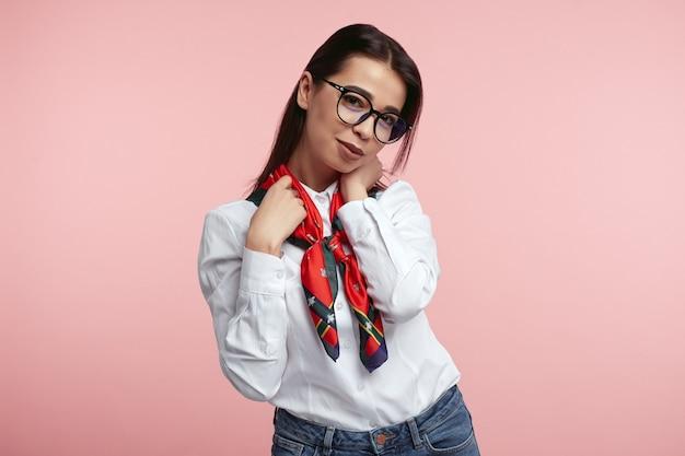 Молодая женщина в белой рубашке и очках имеет счастливое выражение