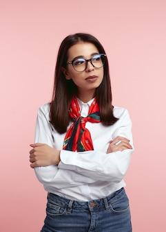 Молодая женщина в белой рубашке и очках, изолированных на розовой стене