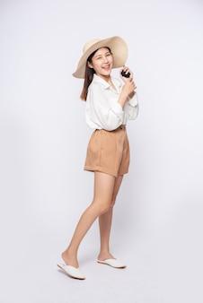Giovane donna che indossa una camicia bianca e pantaloncini, indossa un cappello e la maniglia sul cappello