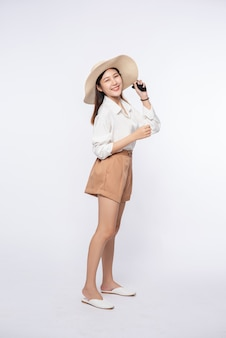 Young woman wearing a white shirt and shorts, wearing a hat and handle on the hat