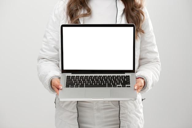 Giovane donna che indossa abiti invernali azienda laptop
