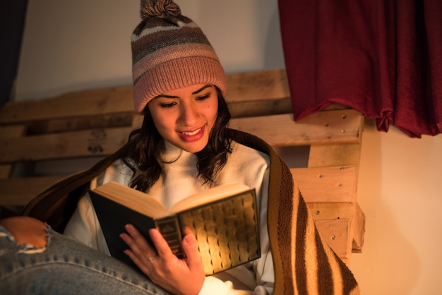Young woman wearing a winter hat reading a book with a pallet behind
