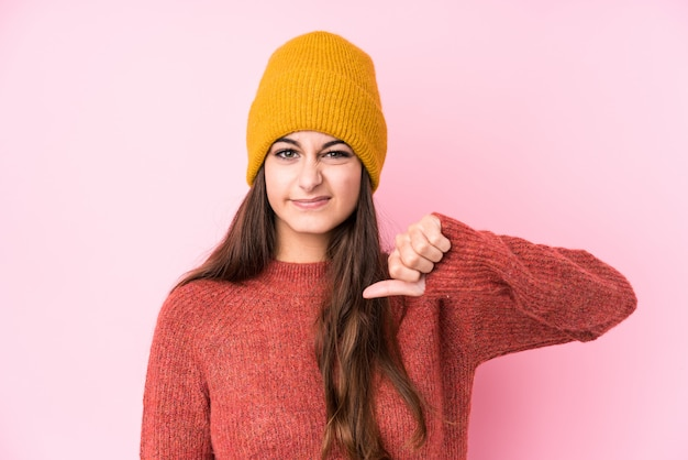 Young woman wearing a wool cap showing a dislike gesture, thumbs down