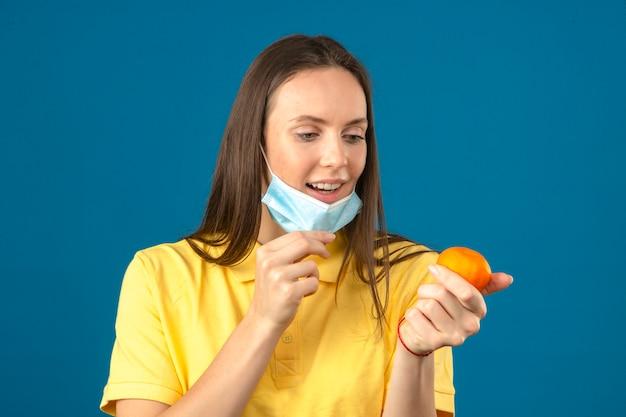 Giovane donna che indossa la camicia di polo gialla che decolla maschera medica protettiva e che tiene mandarino arancio che esamina agrume a disposizione su fondo blu