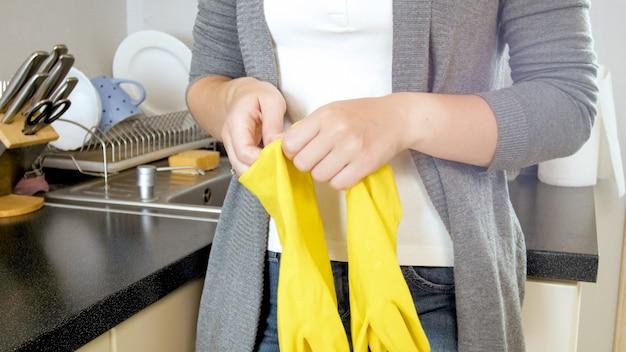 キッチンを掃除する前に黄色のゴム手袋を着用している若い女性。