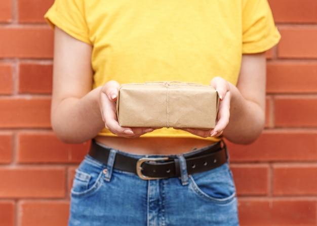 Молодая женщина в желтой рубашке, держа подарок к кирпичной стене