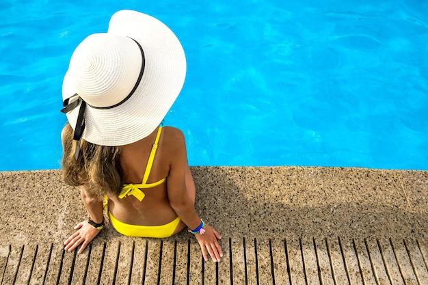 夏の晴れた日に、澄んだ青い水のプールの近くで休んでいる黄色い麦わら帽子をかぶった若い女性。