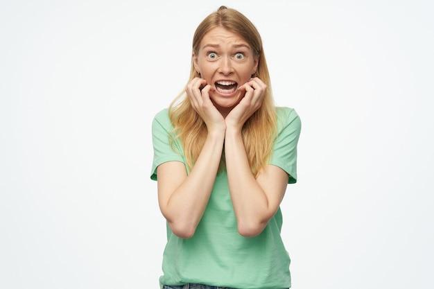 若い女性は、緑のtシャツを着て、幸せで満足していると感じ、誰かと浮気します
