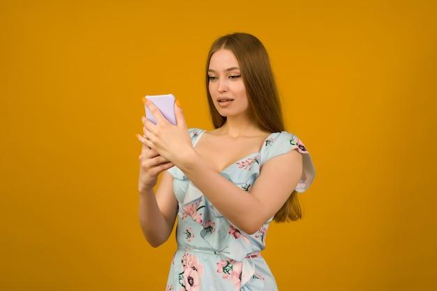若い女性はスマートフォンのニュースに驚いた花と日光浴ドレスを着ています