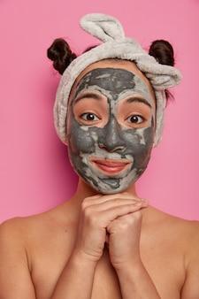 La giovane donna indossa trattamenti per la pelle della maschera di argilla facciale naturale dopo aver fatto il bagno