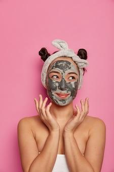 젊은 여성이 목욕 후 천연 페이셜 클레이 마스크 스킨 트리트먼트를 착용합니다.
